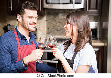 Couple toasting wine while cooking in kitchen