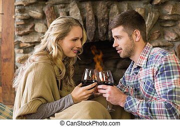 Couple toasting wineglasses in front of lit fireplace - Side...