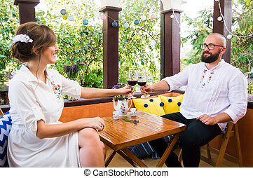 Couple toasting with a glass of wine on date