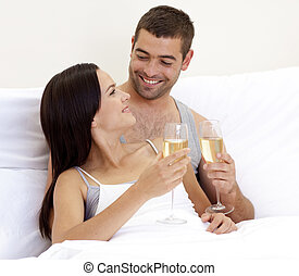 Couple toasting with champagne glasses in bed - Happy young...