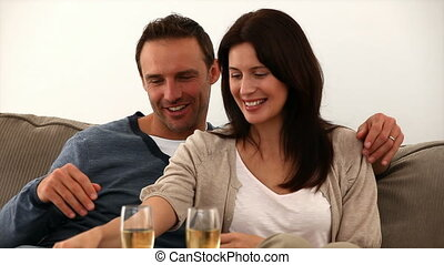 Couple toasting with champagne on the sofa