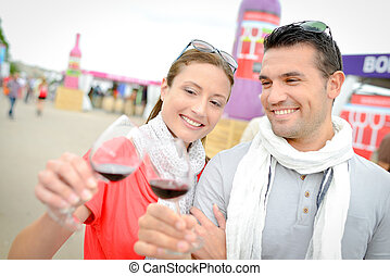 Couple toasting with red wine at wine event