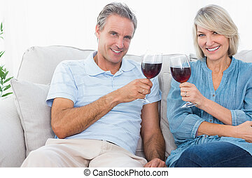 Couple toasting with red wine on the sofa looking at camera