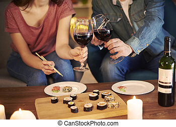 Couple toasting with red wine over date