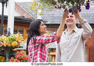 Couple touching flowers in hanging basket