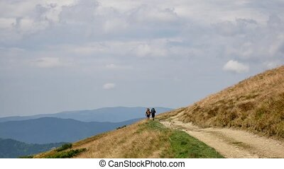 Couple Tourists on top of mountain looking at mountains. Hiker couple travel enjoy life scenic nature landscape. Summer vacation travel adventure. Backpackers trekking mountains summer hike.