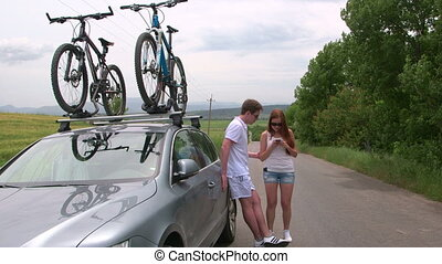 Couple traveling by car with two bicycles mounted on bike roof carrier