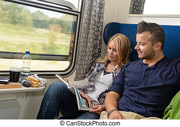 Couple traveling by train reading magazine smiling