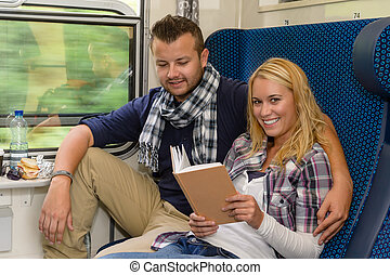 Couple traveling by train woman reading smiling