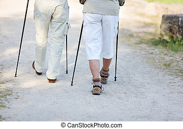 Couple traveling with nordic walking sticks