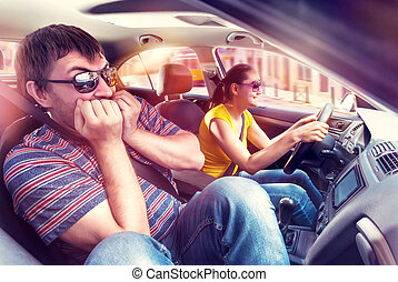 Couple travelling by car, woman is driving, man is very...