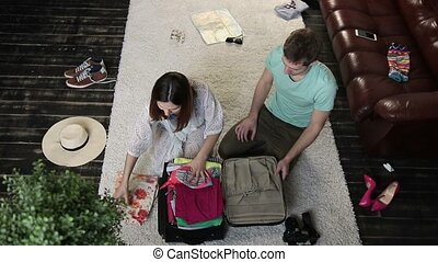 Couple trying to close overfilled suitcase