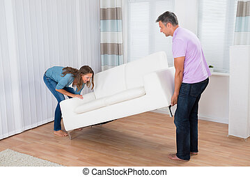Couple Trying To Move A Couch - Couple Trying Hard To Move A...