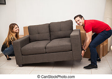 Couple trying to move a sofa