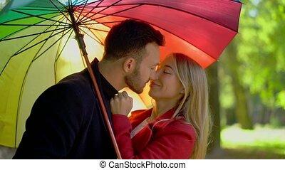 Couple under rainbow umbrella walking in park - Couple In...