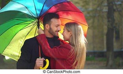Couple under rainbow umbrella walking in park - Hugging...