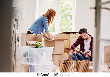 Couple unpacking stuff from carton boxes while moving-into new home