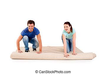 couple unrolling a carpet