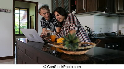 Couple Use Laptop Computer, Young Woman And Man In Kitchen Studio Talking Modern House Interior