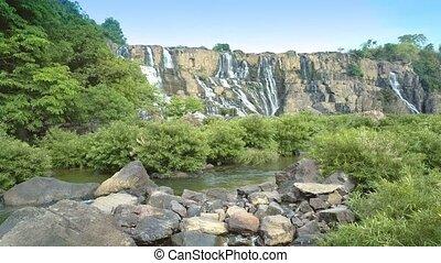 couple uses stone as viewpoint to enjoy waterfall - splendid...