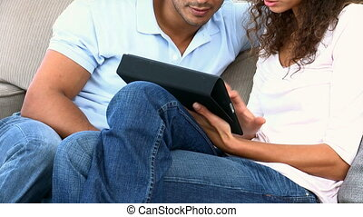 Couple using a computer tablet sitt