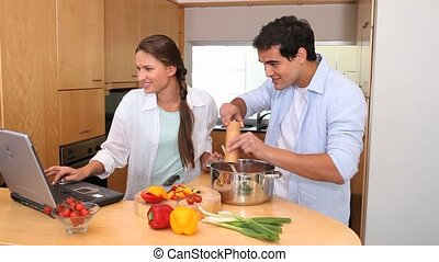 Couple using a laptop are cooking together