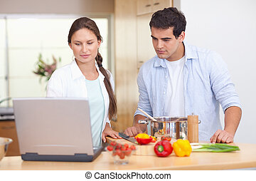 Couple using a laptop to cook