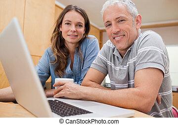Couple using a laptop while having tea