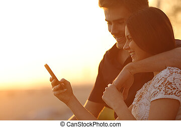 Couple using a smartphone in a sunset back light - Happy...