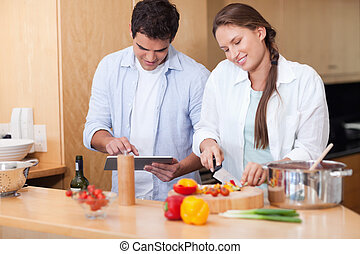 Couple using a tablet computer to cook