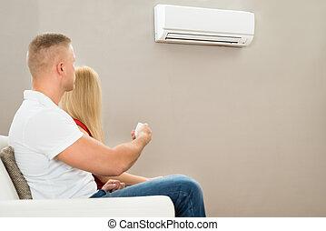 Couple Using Air Conditioner