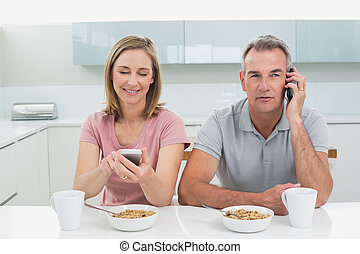 Couple using cell phones while having breakfast in kitchen