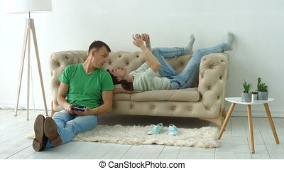Couple using digital devices on cozy couch at home