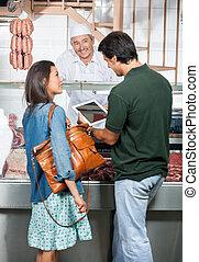 Couple Using Digital Tablet At Butcher Shop