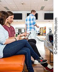 Couple Using Digital Tablet in Bowling Club
