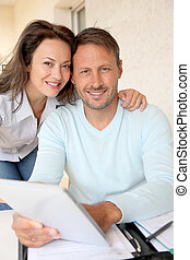 Couple using electronic tablet at home