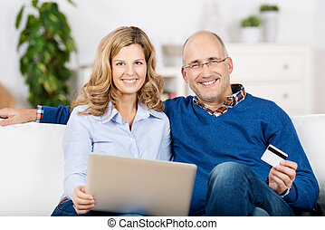Couple Using Laptop And Credit Card For Online Shopping