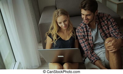 Couple using laptop at home.