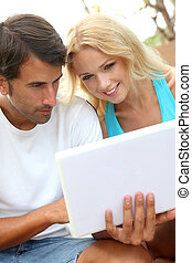 Couple using laptop computer outside