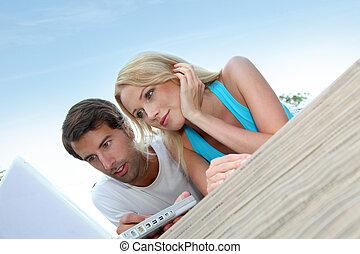 Couple using laptop computer outside