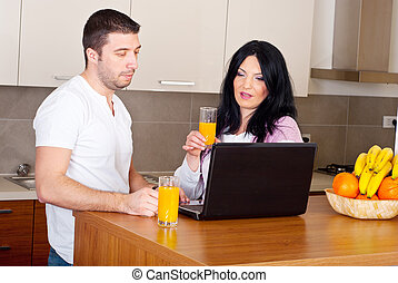 Couple using laptop in their kitchen