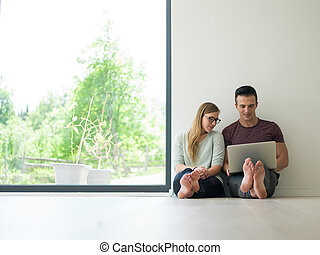 couple using laptop on the floor at home
