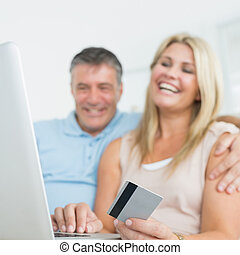 Couple using laptop on the sofa to