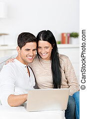 Couple Using Laptop Together While Sitting On Sofa