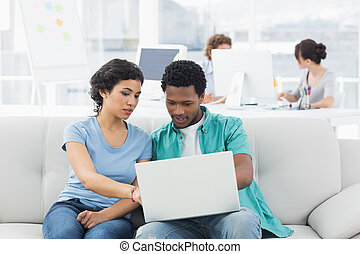 Couple using laptop with colleagues at creative office