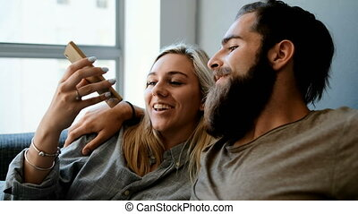 Couple using mobile phone and laptop in living room 4k -...