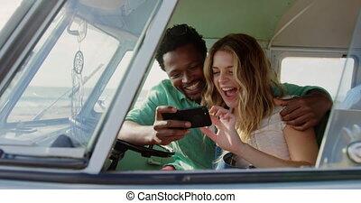 Couple using mobile phone in camper van 4k