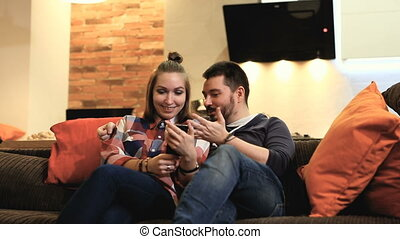 Couple using mobile phone smiling and having fun.