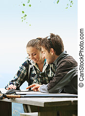 Couple using tablet on the mountain