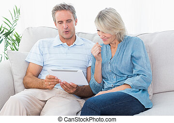 Couple using tablet together on the couch
